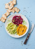 Variations of hummus and crackers. Pumpkin, turmeric, avocado, beetroot hummus with olive oil, sesame seeds and micro greens on a. Blue background, top view Royalty Free Stock Image