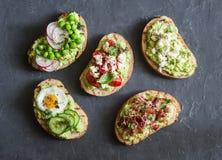 Variationsavokadosmörgås - med frasig bacon, vaktelägg, tomater, getost, gröna ärtor, rädisa, gurka sunt mellanmål royaltyfria foton