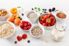 Variaty of raw cereals, fruits and nuts for breakfast. Oatmeal f Royalty Free Stock Images