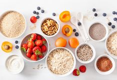 Variaty of raw cereals, fruits and nuts for breakfast. Oatmeal f Stock Image