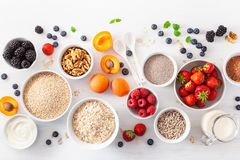Variaty of raw cereals, fruits and nuts for breakfast. Oatmeal f Stock Images
