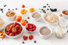 Variaty of raw cereals, fruits and nuts for breakfast. Oatmeal f Royalty Free Stock Image