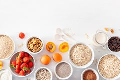 Variaty of raw cereals, fruits and nuts for breakfast. Oatmeal f Stock Photo
