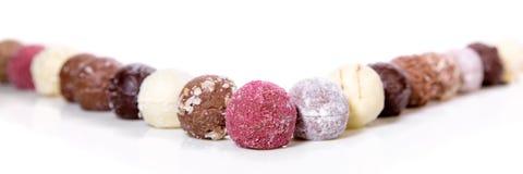 Variazione dei tartufi di cioccolato o delle praline gastronomici sul BAC bianco Fotografie Stock Libere da Diritti