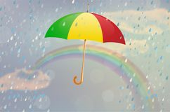 Varicolored opened umbrella with rain, rainbow and cloudy sky Royalty Free Stock Image