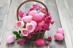 Varicolored pink Easter eggs in wicker basket Royalty Free Stock Photography