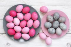 Pink and grey Easter eggs. Varicolored pink and grey Easter eggs in plates on rustic white wooden table. Top view point royalty free stock photography