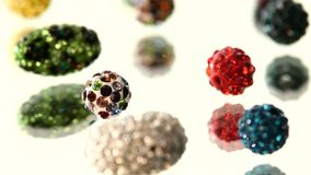 Varicolored, shiny beads on white background, cam. A lot of shiny, different colorful beads isolated on white background, cam moves to the left, rotation, close stock video footage
