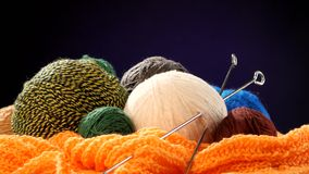 Varicolored yarn balls with spokes on orange scarf. Colorful and varicolored yarn balls with silver spokes on orange scarf on black background stock video footage