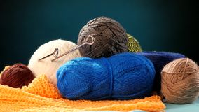 Varicolored yarn balls with spokes on orange scarf. Colorful and varicolored yarn balls with silver spokes on orange scarf on blue background, cam moves to the stock footage