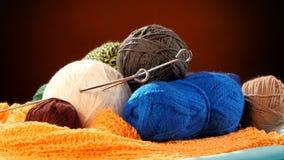 Varicolored yarn balls with spokes on orange scarf stock video footage