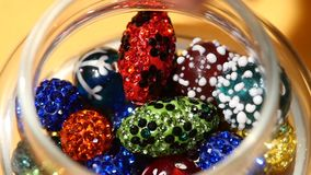Varicoloured beads falls into the jar on yellow stock video