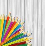 Varicoloured Bleistifte auf einer hölzernen Beschaffenheit des Hintergrundes vektor abbildung