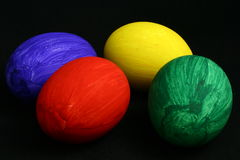 Varicoloured Eggs On Black. Red yellow dark blue and green egg on a black background Royalty Free Stock Photos