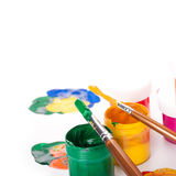 Varicoloured paints and brushes on a white Stock Images