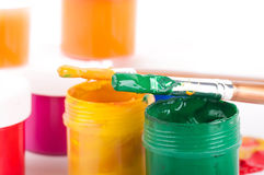 Varicoloured paints and brushes on a white backgro Stock Photos