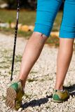 Varicose veins. Woman with varicose veins on a leg walking using trekking poles royalty free stock images