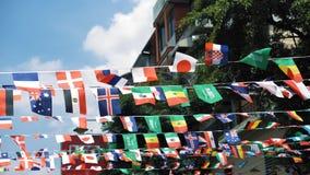 Varie bandiere nazionali che ondeggiano nell'aria al giorno soleggiato Bandiere come attributo dell'evento del mondo archivi video
