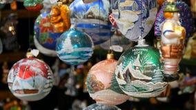 Varie bei palle e giocattoli di Natale per decorare l'abete di Natale sul contatore del mercato Iscrizione in tedesco video d archivio