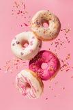 Varie ciambelle decorate nel moto che cade sul fondo rosa Immagini Stock Libere da Diritti