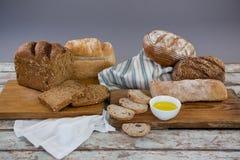 Varie pagnotte del pane con burro su superficie di legno Fotografia Stock Libera da Diritti