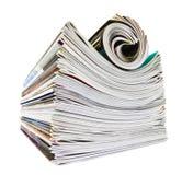 Varie riviste impilate e rotolate sopra bianco Fotografia Stock