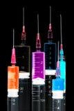 Varie siringhe riempite di liquidi colorati Fotografia Stock