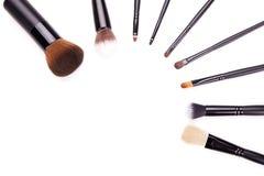 Varie spazzole di trucco isolate sopra fondo bianco, insieme piano di vista superiore delle spazzole professionali essenziali di  Fotografia Stock