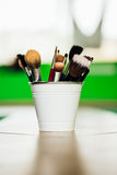 Varie spazzole e matite di trucco su fondo verde chiaro dentro il secchio il pavimento Copyspace Fotografia Stock Libera da Diritti