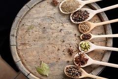 Varie spezie aromatiche Colourful per la cottura sul barilotto di legno vecchio, primo piano, disposizione piana, fuoco selettivo Immagini Stock Libere da Diritti
