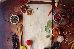 Varie spezie indiane in cucchiai di legno, in semi, in erbe e nel bordo di legno matto e vuoto Fotografia Stock