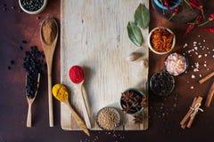 Varie spezie indiane in cucchiai di legno, in semi, in erbe e nel bordo di legno matto e vuoto Fotografie Stock Libere da Diritti
