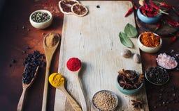 Varie spezie indiane in cucchiai di legno, in semi, in erbe e nel bordo di legno matto e vuoto Fotografia Stock Libera da Diritti