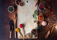 Varie spezie indiane in cucchiai di legno, in semi, in erbe e nel bordo di legno matto e vuoto Immagini Stock