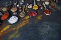 Varie spezie indiane in cucchiai e ciotole e dadi di legno del metallo sulla tavola di pietra scura Spezie variopinte, fuoco sele Fotografie Stock