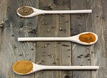 Varie spezie sui cucchiai di legno e sul fondo di legno d'annata immagine stock