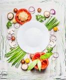 Varie verdure e condimento che cucinano gli ingredienti intorno al piatto in bianco su fondo di legno rustico leggero, vista supe fotografia stock libera da diritti
