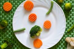 Varie verdure miste su un piatto bianco e su un fondo verde Fotografia Stock