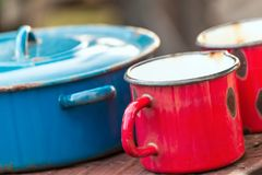 Enamelled rusty pots. Varied ancient enamel pots partially damaged by rust Stock Photography