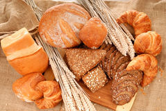 Varied bread display. Variety of nutritional breads, ranging from simple white to whole wheat, freshly home baked on burlap, jute cloth Stock Images