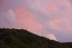 Varied in colour clouds above mountains. Stock Photos