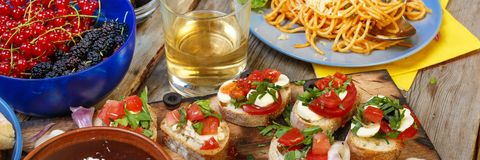 Free Varied Snacks On The Dining Table, Wine, Pasta And Bruschettes With Avocado And Cherry Tomatoes Closeup. Royalty Free Stock Photography - 100355027