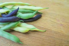 Varied varieties of green asparagus beans lie on a wooden surface. A variety of varieties of young green asparagus beans of green yellow and purple colors lie on stock photo