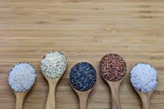 Variedad de arroz en la cuchara de madera en el fondo de madera Foto de archivo