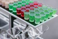 Variedad de bebida fresca verde colorida del alcohol de las pistolas del cóctel dulce hermoso rojo y blanco de los tiros en peque Fotos de archivo libres de regalías