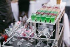 Variedad de bebida fresca verde colorida del alcohol de las pistolas del cóctel dulce hermoso rojo y blanco de los tiros en peque Imágenes de archivo libres de regalías