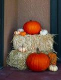 Variedad de calabazas en Hay Bales - decoración de Halloween de la caída al lado de la entrada del hogar Foto de archivo libre de regalías