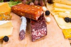 Variedad de carnes y de quesos curados en el tablero de madera Imágenes de archivo libres de regalías