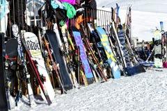 Variedad de cielos y de snowboard que se colocan fuera de una barra de la montaña Imagen de archivo