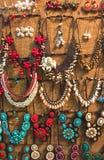 Variedad de collares plásticos de piedra coloridos de la joyería del brillo creativo hermoso que cuelgan en la pared para la vent Imagenes de archivo